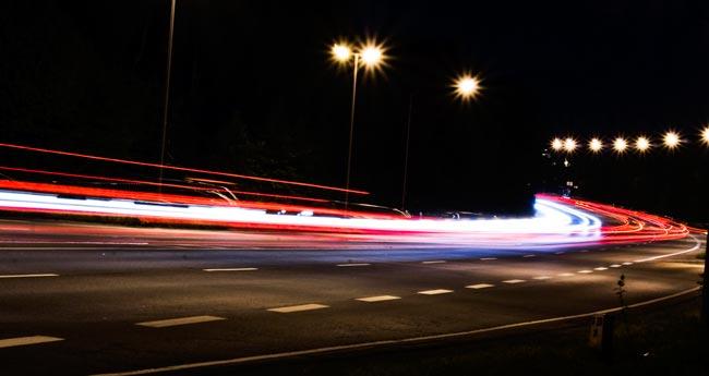 Das Licht verschwimmt, da der Weg des Lichtes der Autos schneller fortgeschritten ist, als die Kamera belichten konnte