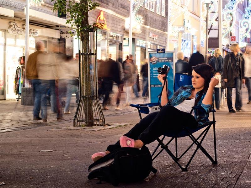 Foto zum Thema Auszeit: eine junge Frau sitzt mitten in einer Einkaufsmeile auf einem Campingstuhl in bequemer Kleidung und schaut ganz entspannt die Straße entlang.