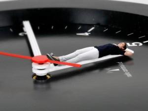 Foto zum Thema Auszeit: eine junge Frau liegt auf einem Uhrzeiger, als sei es eine Liege.