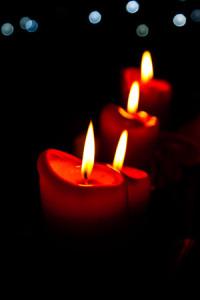 Kerzen die hintereinander stehen und von vorne, bis nach hinten immer unschärfer werden. Im Hintergrund sieht man verschwommene Lichter eines Weihnachtsbaumes