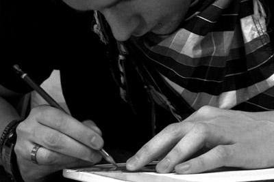 Bild eines Zeichnenden, der konzentriert über einem Blatt Papier arbeitet.
