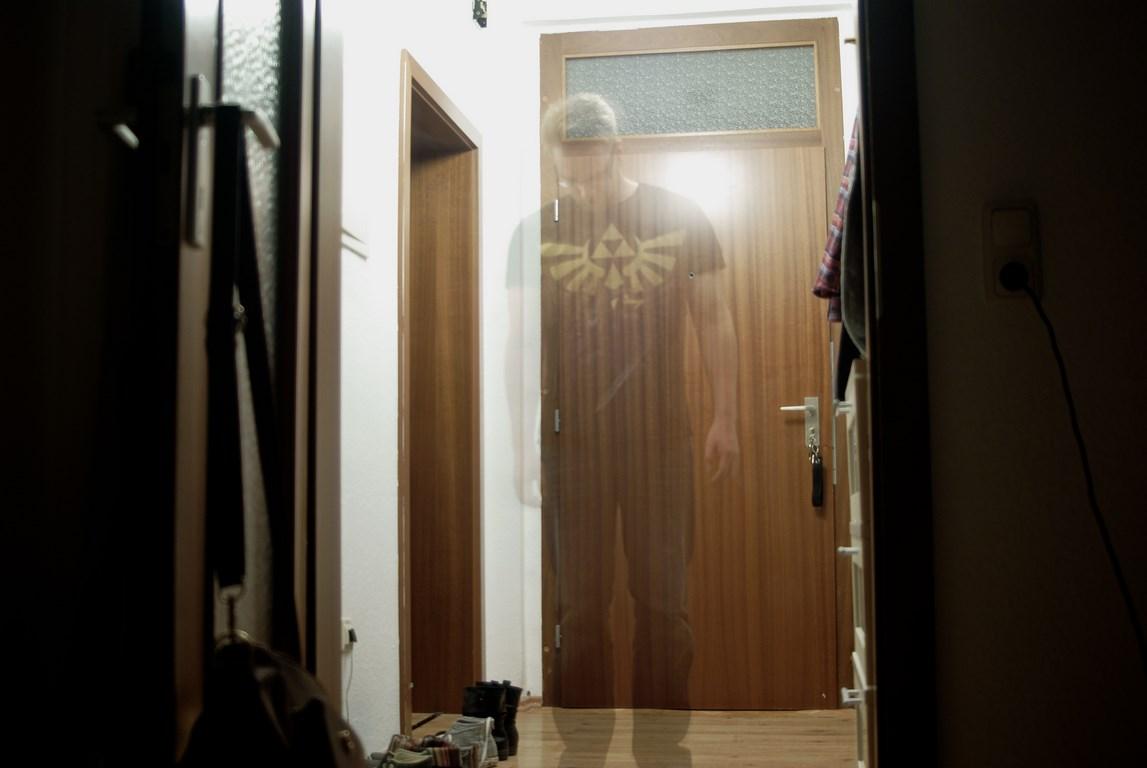Eine Person im Geisteffekt Langzeitbellichtung die im Flur steht und durchsichtig ist. Der Kopf ist gesenkt.