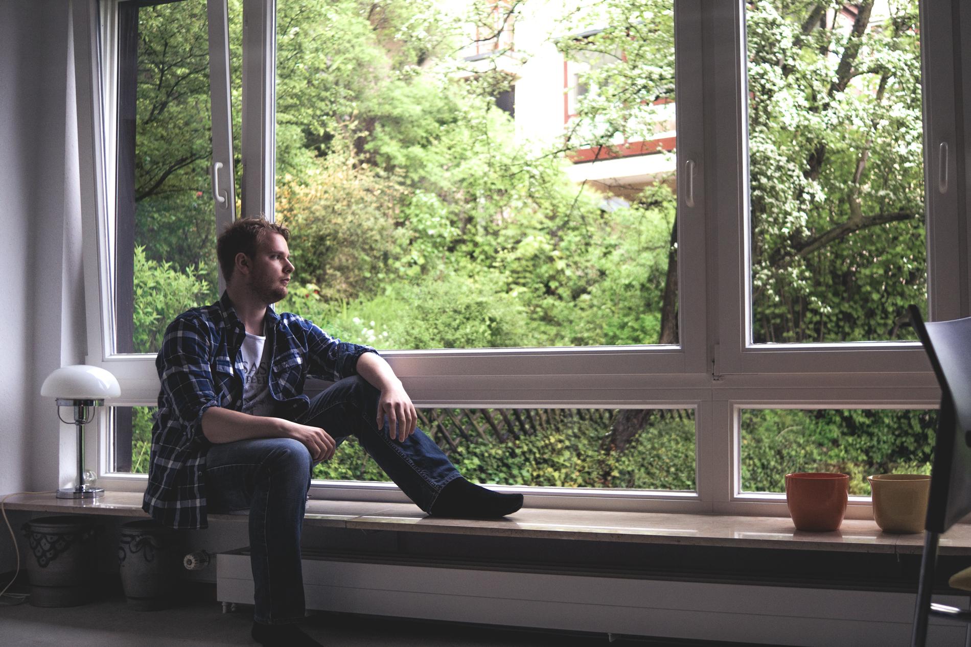 ich, wie ich am Fenster sitze und nach draußen in den Regen schaue